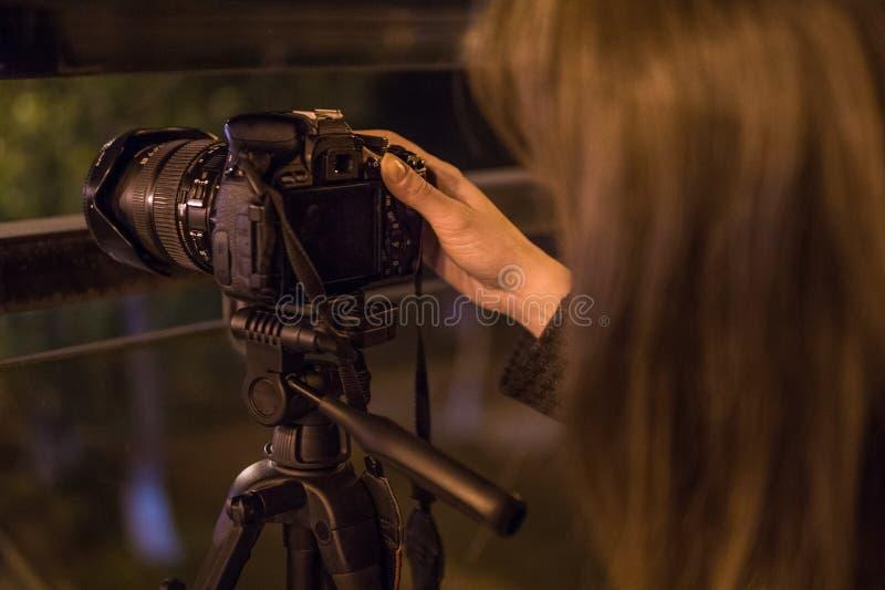 Jonge vrouw die cameravertoning bekijken bij nacht, close-up stock foto
