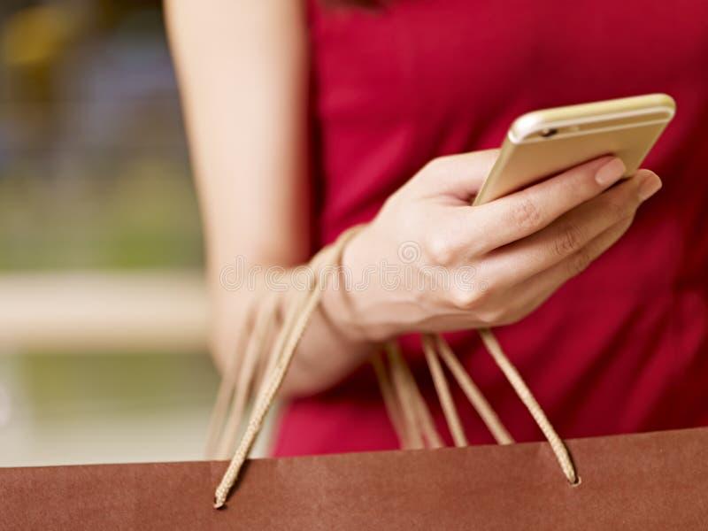 Jonge vrouw die cellphone gebruiken terwijl het winkelen stock foto