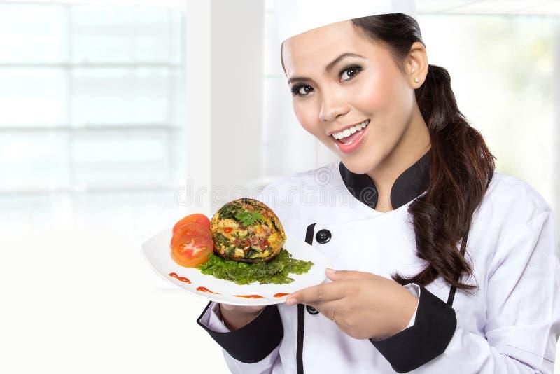 Jonge vrouw die Chef-kok voorstellen stock fotografie