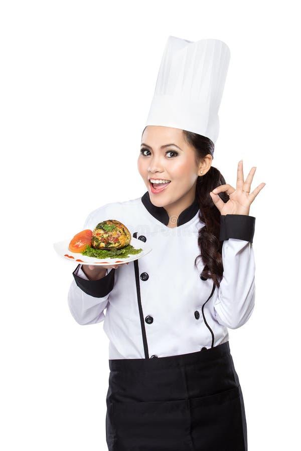 Jonge vrouw die Chef-kok voorstellen stock foto's
