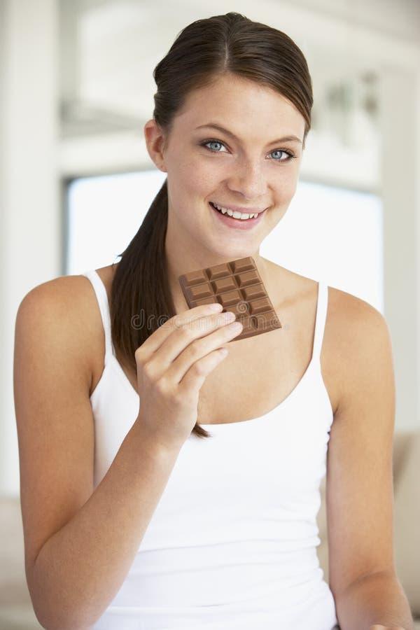 Jonge Vrouw die Chocolade eet stock foto's