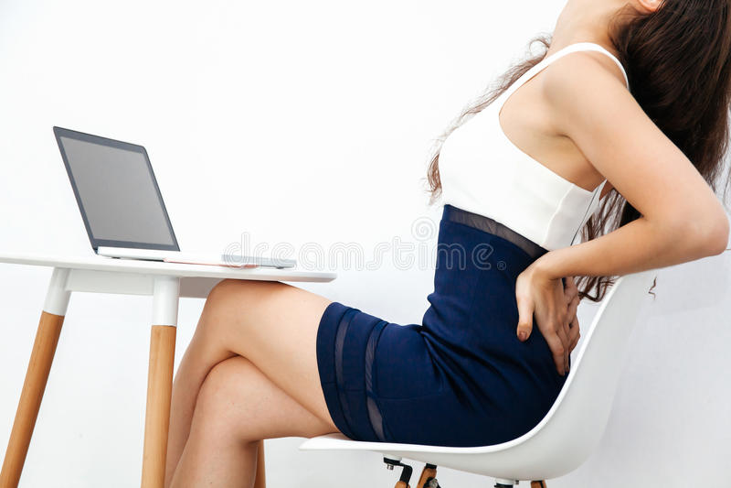 Jonge vrouw die chronische rugpijn/rugpijn/bureausyndroom hebben terwijl het werken met laptop aan wit bureau royalty-vrije stock fotografie