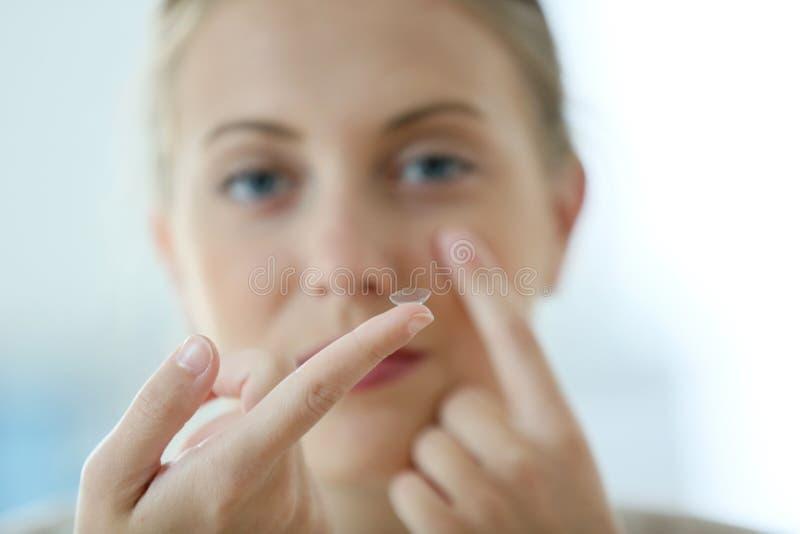 Jonge vrouw die contactlenzen aanbrengen stock foto