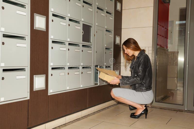 Jonge vrouw die correspondentie van brievenbus nemen stock afbeelding