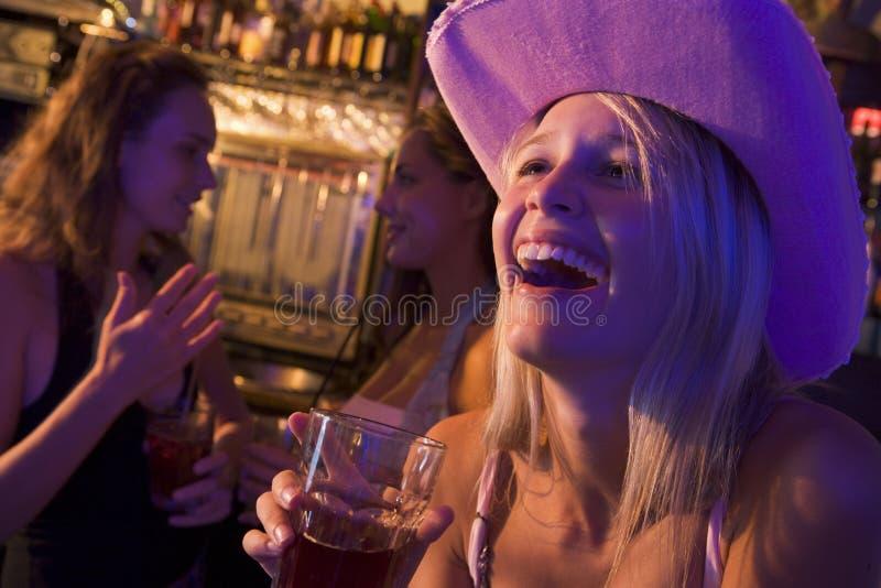 Jonge vrouw die in cowboyhoed bij een nachtclub lacht stock afbeelding