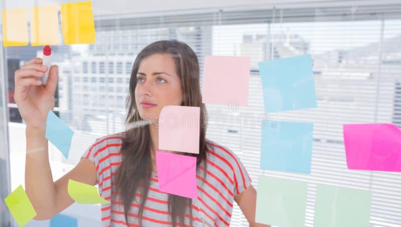 Jonge vrouw die in creatief bureau schrijven royalty-vrije stock afbeeldingen