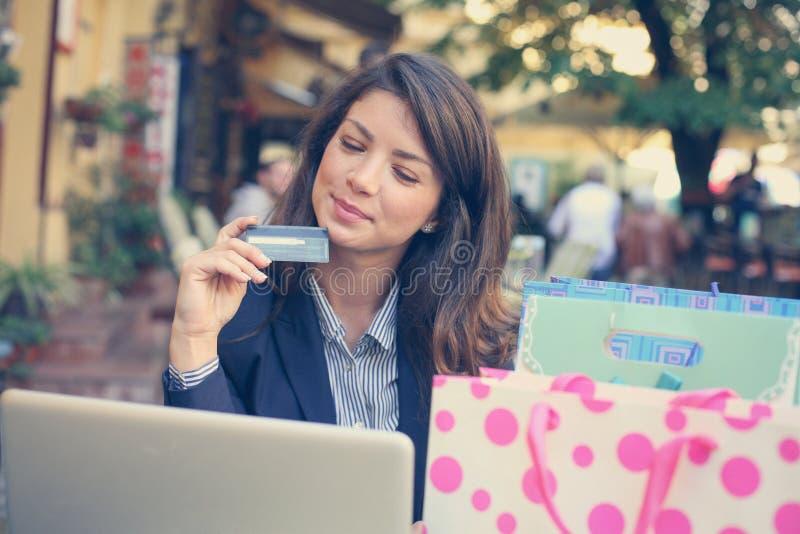 Jonge vrouw die creditcard gebruiken om online te winkelen stock foto