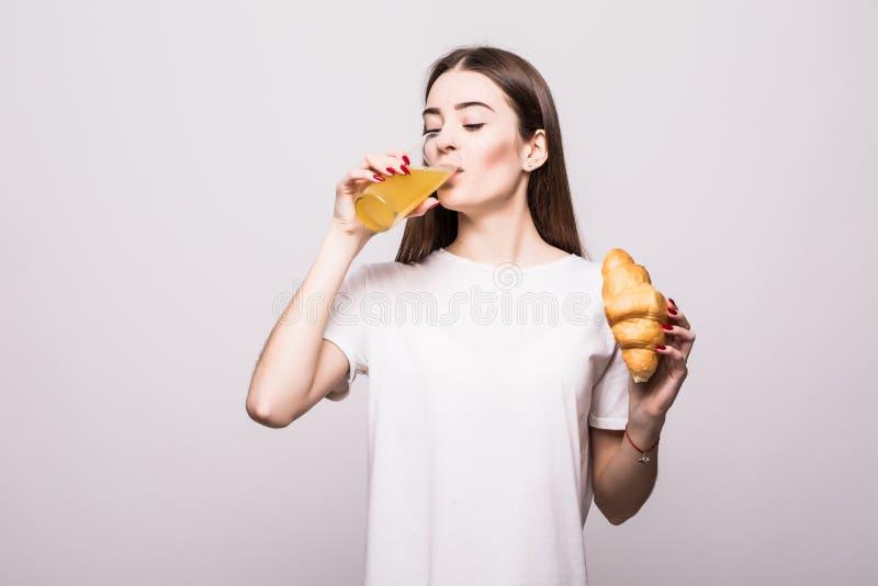 Jonge vrouw die croissant met jus d'orange op witte achtergrond eten royalty-vrije stock fotografie