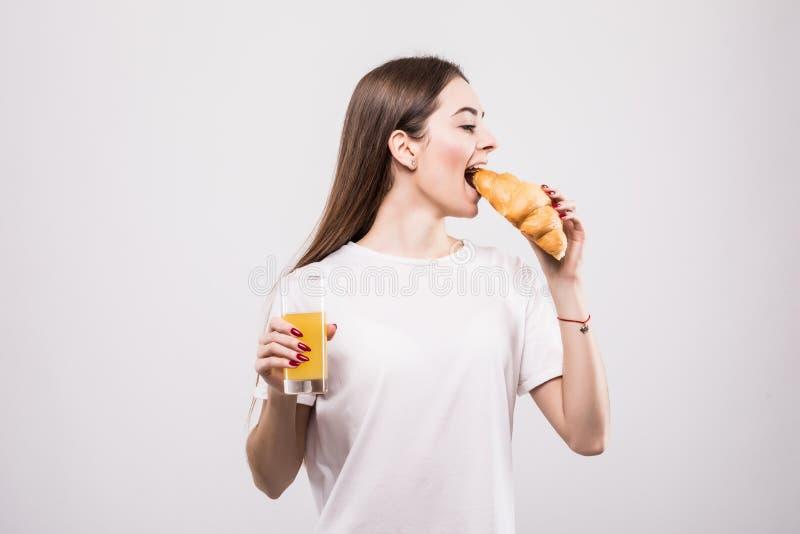 Jonge vrouw die croissant met jus d'orange op witte achtergrond eten royalty-vrije stock afbeelding