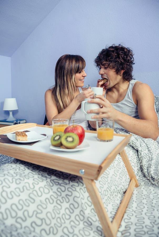 Jonge vrouw die de gelukkige mens in bedontbijt voeden stock afbeelding