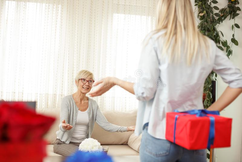 Jonge vrouw die de giftdoos achter de rug voor haar moeder houden Comfortabele woonkamer royalty-vrije stock foto