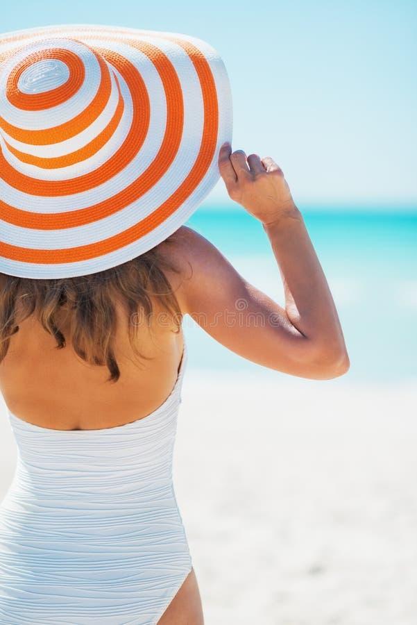 Jonge vrouw die in de hoed van het zwempakstrand afstand onderzoeken royalty-vrije stock afbeelding