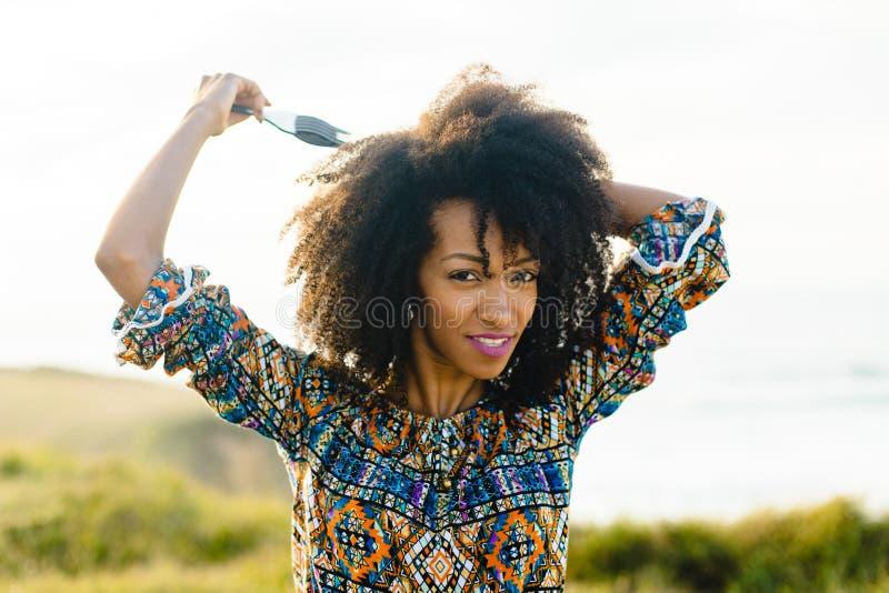 Jonge vrouw die de kam van het afrohaar gebruikt royalty-vrije stock afbeeldingen