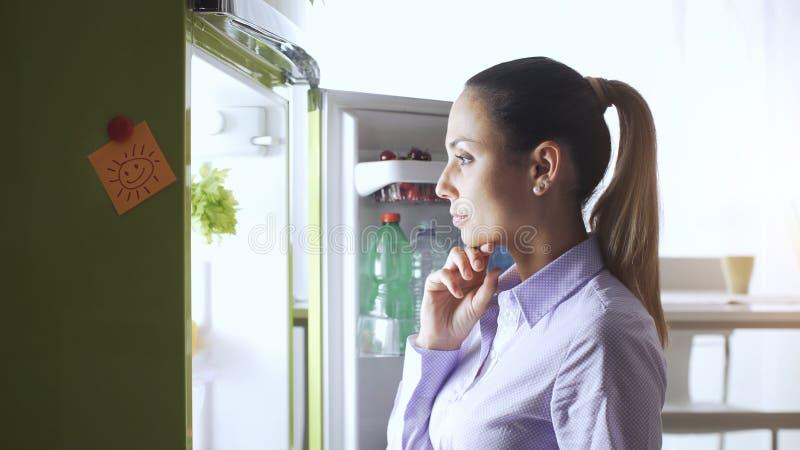 Jonge vrouw die de koelkast onderzoeken stock foto's