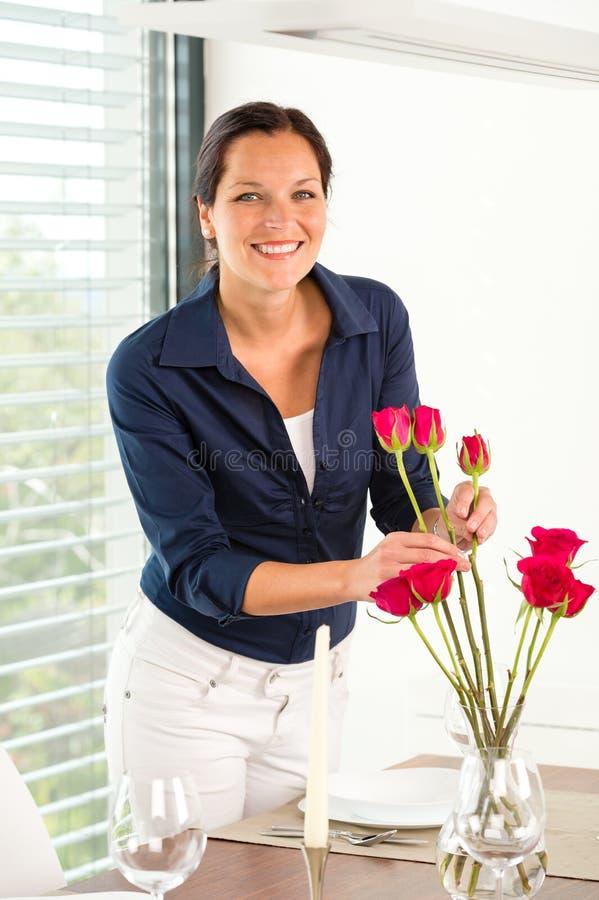 Jonge vrouw die de lijst van het bloemendiner schikken stock afbeelding