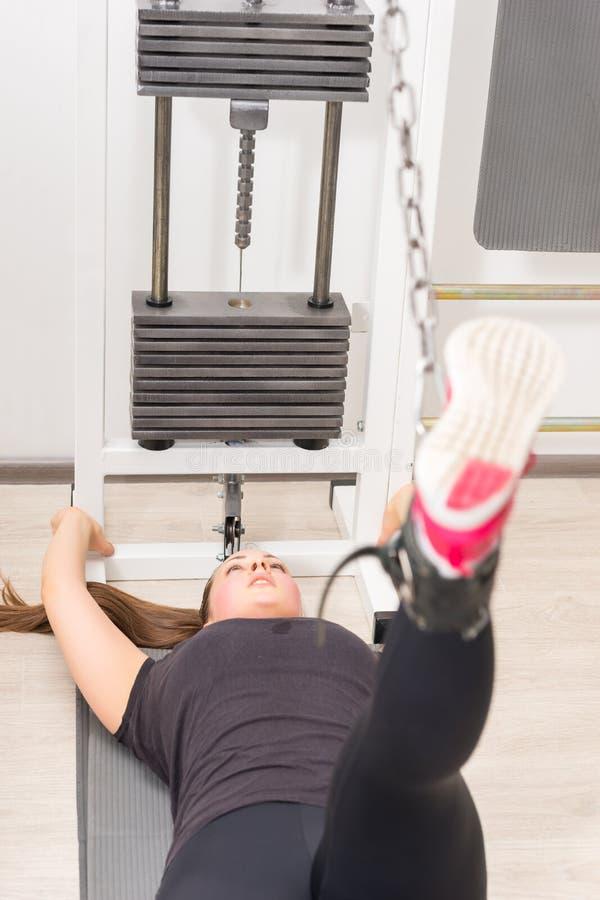 Jonge vrouw die de machine van de kabeloversteekplaats met behulp van bij gymnastiek royalty-vrije stock foto's