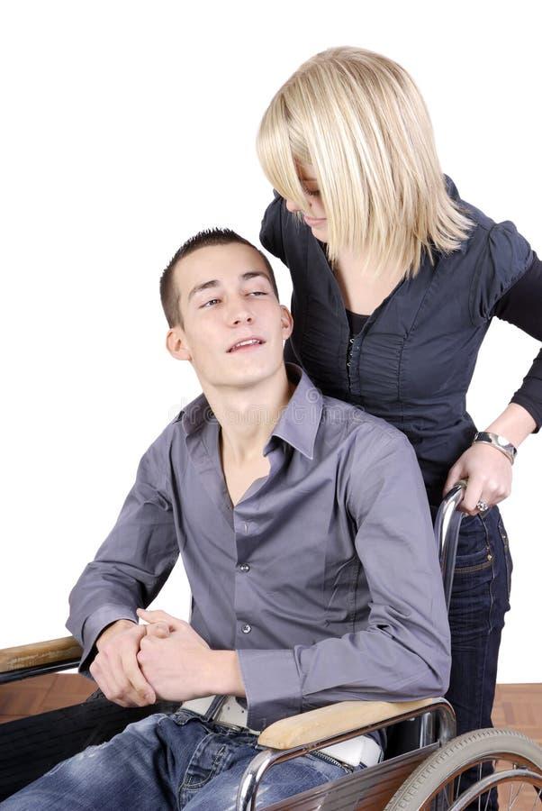 Jonge vrouw die de mens in rolstoel behandelt royalty-vrije stock afbeelding