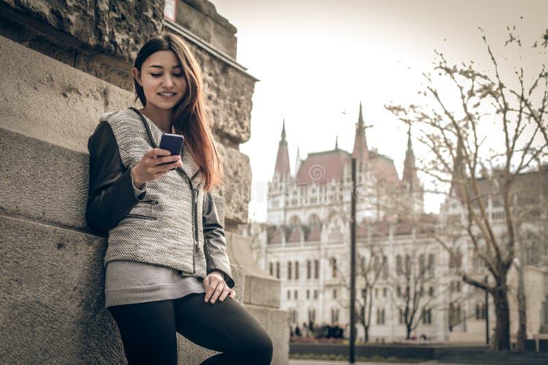 Jonge vrouw die de mobiele telefoon bekijken stock afbeeldingen