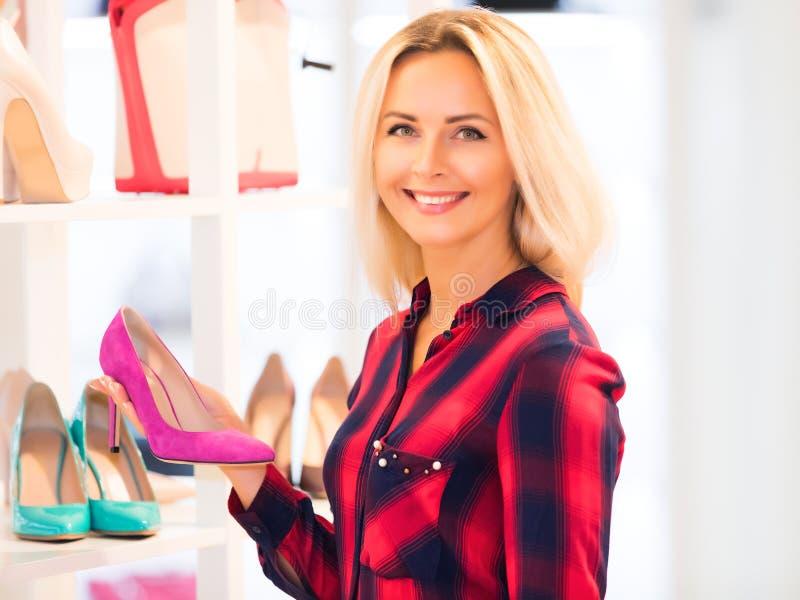 Jonge vrouw die in de opslag van het manierschoeisel winkelen stock foto