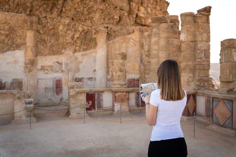Jonge vrouw die de ruïnes van masada in Israël onderzoeken stock afbeeldingen