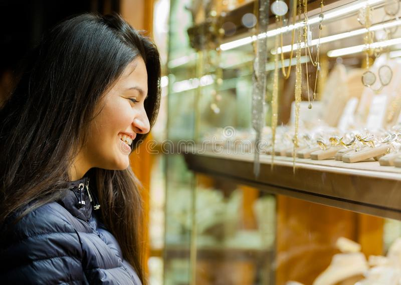 Jonge vrouw die de showcase van openluchtjuwelen bekijken stock afbeelding