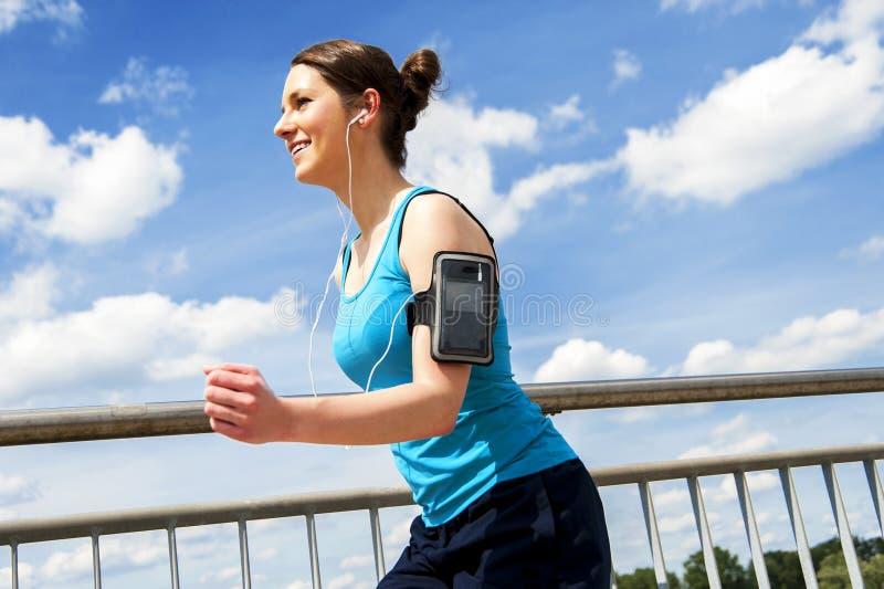Jonge vrouw die in de stad over brige in zonlicht lopen, smil royalty-vrije stock foto