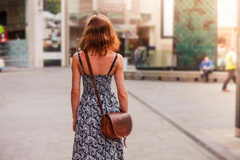 Jonge vrouw die in de straat loopt stock foto