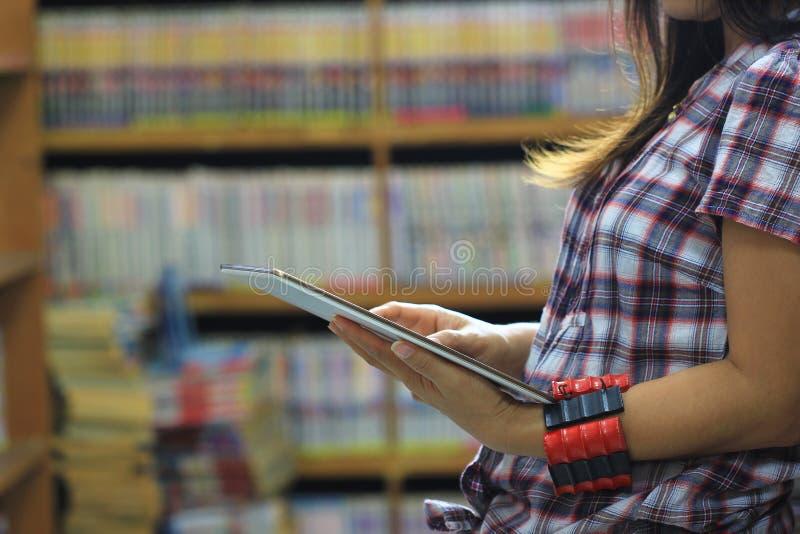 Jonge vrouw die de tablet in bibliotheekruimte en boekenrekachtergrond, Technologie en Onderwijsconcept gebruiken royalty-vrije stock fotografie