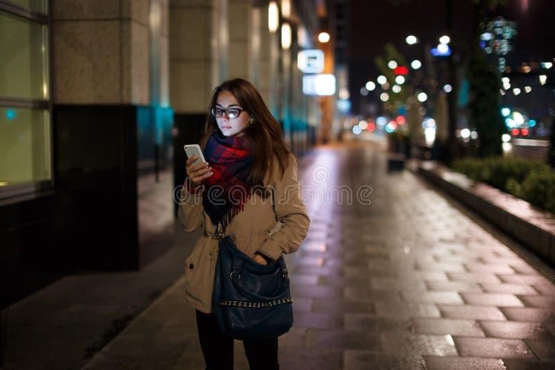 Jonge vrouw die de telefoon bij nacht bekijken royalty-vrije stock afbeelding