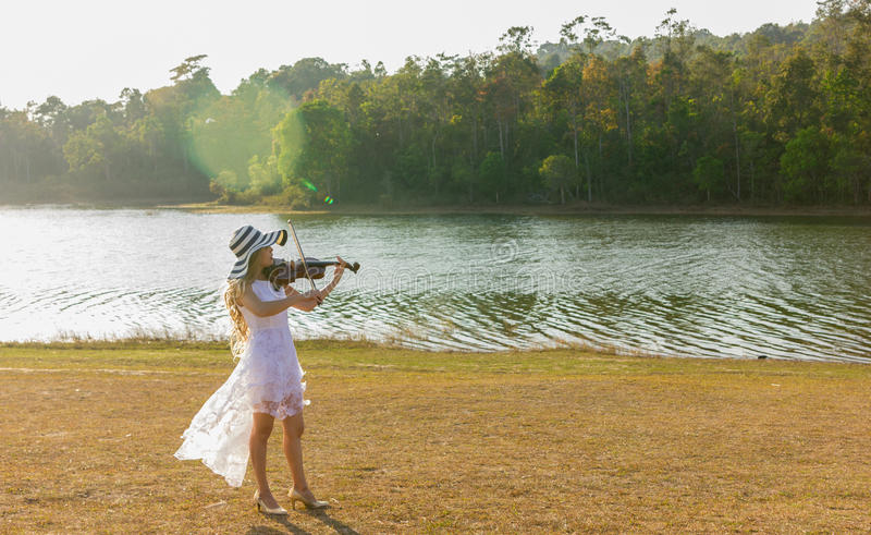 Jonge vrouw die de viool op aardachtergrond spelen royalty-vrije stock afbeelding
