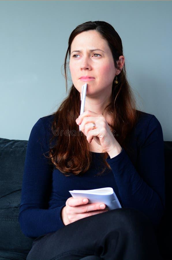 Jonge vrouw die denken over lijst thuis te doen stock foto