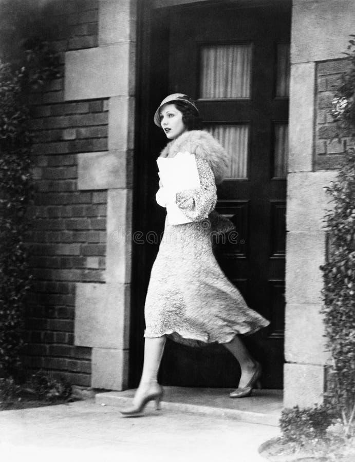 Jonge vrouw die deur opstappen (Alle afgeschilderde personen leven niet langer en geen landgoed bestaat Leveranciersgaranties die stock foto's