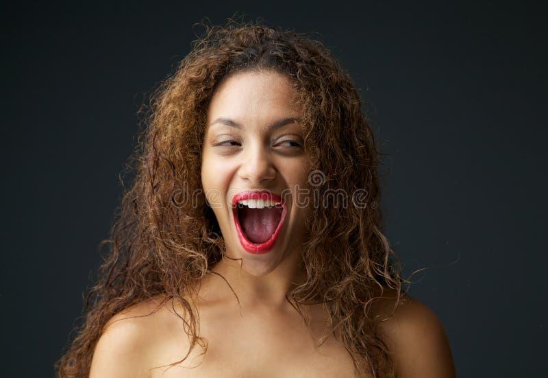 Jonge vrouw die die en met open mond wordt opgewekt lachen royalty-vrije stock afbeeldingen