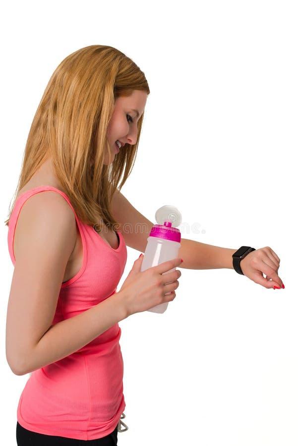 Jonge vrouw die digitaal horloge met fles bekijken royalty-vrije stock foto