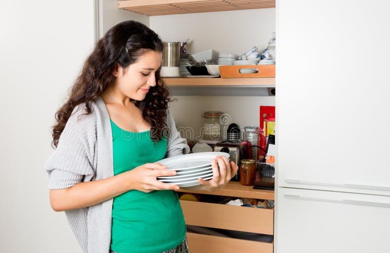 Jonge vrouw die dishware van de kast nemen om de lijst te plaatsen royalty-vrije stock foto