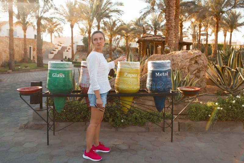 Jonge vrouw die document wegdoen, die het werpen in een gele vaas in park Mooi wijfje in vrijetijdskleding en tennisschoenenzorg stock foto's