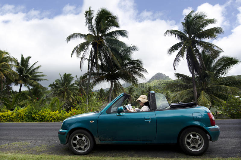 Jonge vrouw die door convertibele auto in een Vreedzaam Eiland reizen stock afbeeldingen