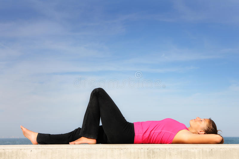 Jonge vrouw die door het overzees rust royalty-vrije stock afbeelding