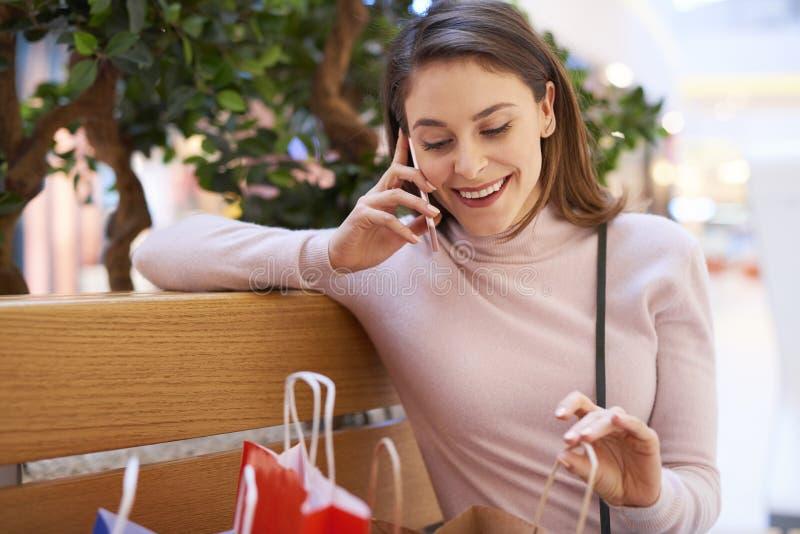 Jonge vrouw die door mobiele telefoon na het grote winkelen spreken stock fotografie