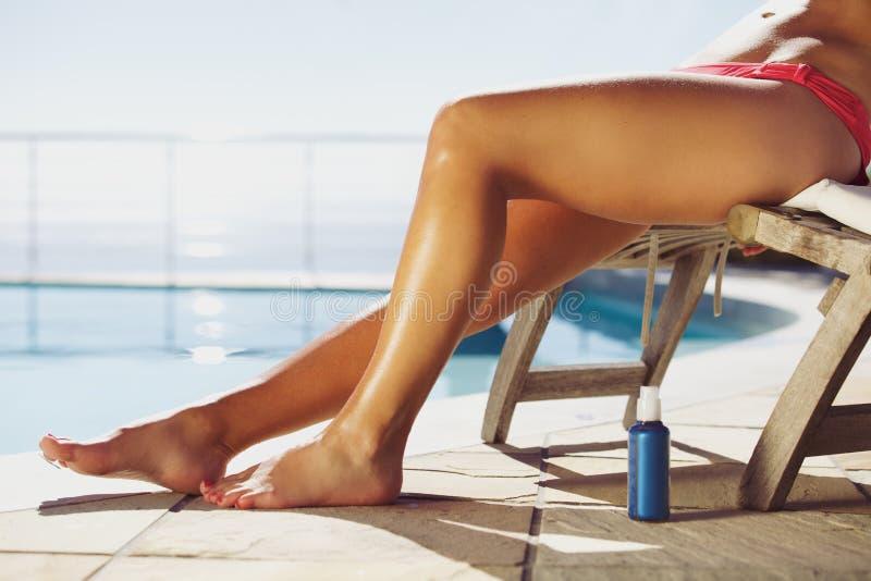 Jonge vrouw die door poolside zonnebaden stock afbeeldingen