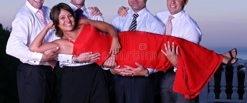 Jonge vrouw die door vier mannen bij een partij wordt opgeheven stock afbeelding