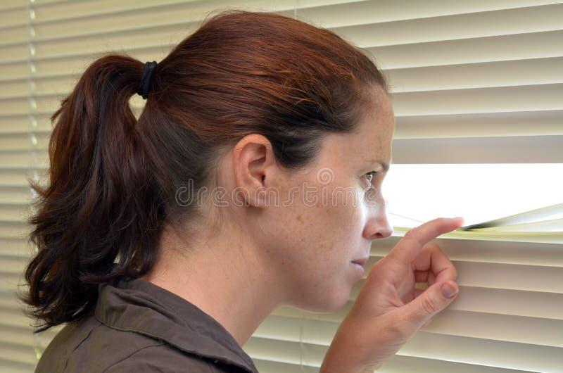 Jonge vrouw die door zonneblinden kijken royalty-vrije stock afbeelding