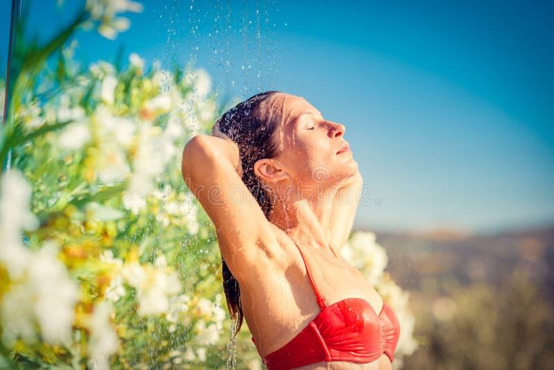 Jonge vrouw die douche neemt stock afbeelding