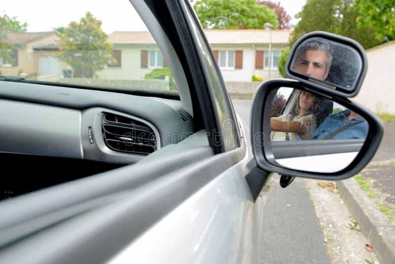 Jonge vrouw die drijfles in auto krijgen stock foto