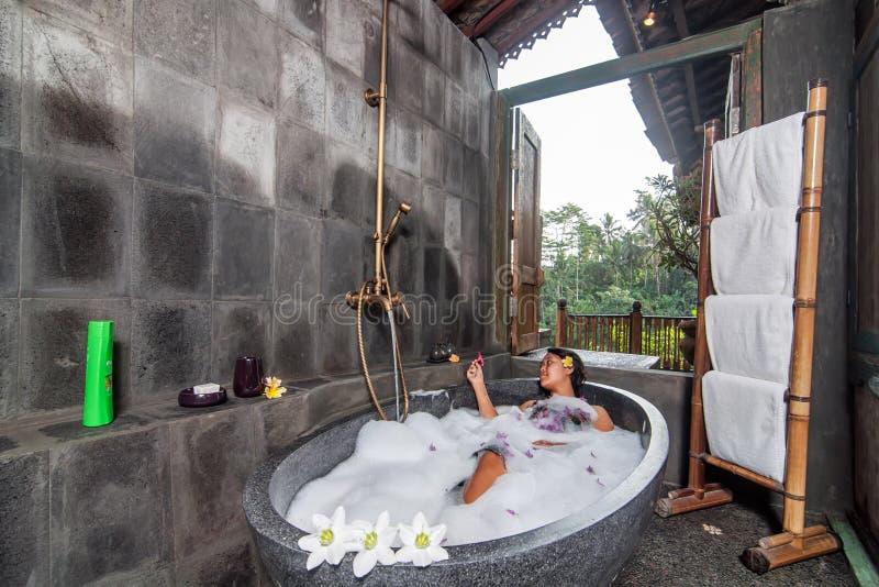 Jonge vrouw die een bad hebben stock afbeelding