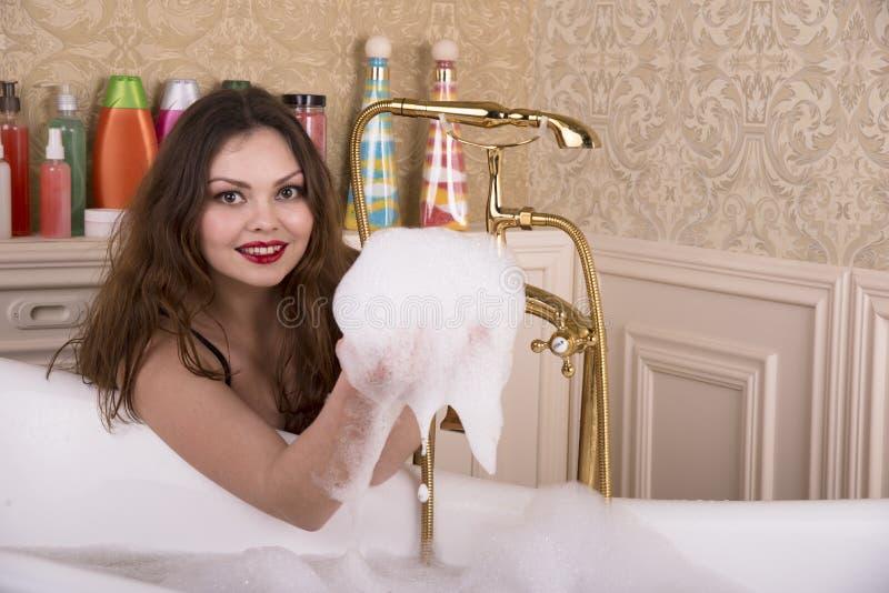 Jonge vrouw die een bad voorbereidingen treffen te nemen stock foto's