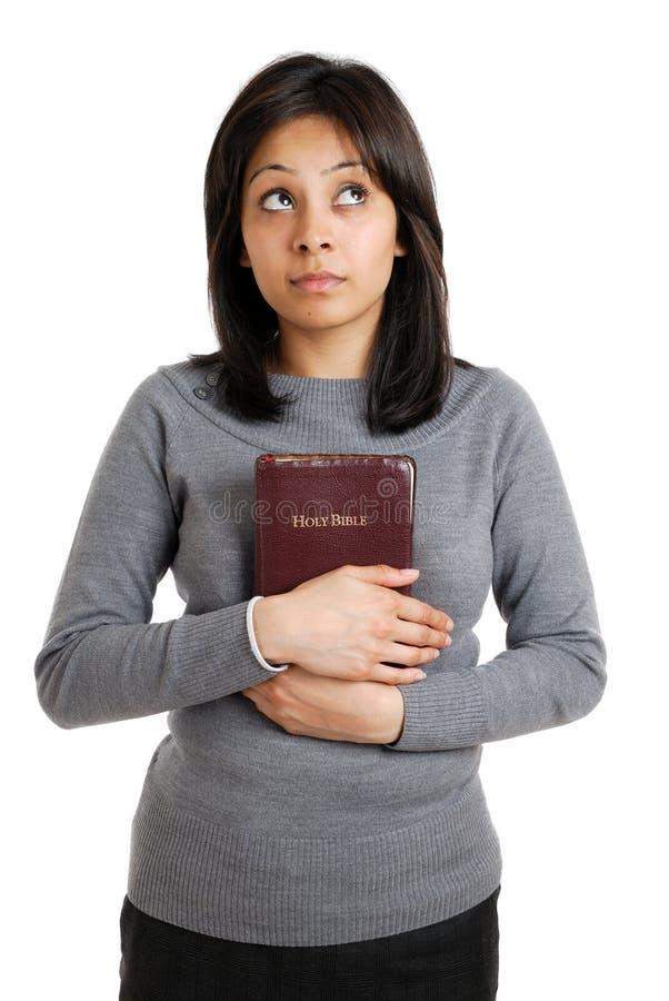 Jonge vrouw die een bijbel houdt terwijl omhoog het kijken stock afbeeldingen