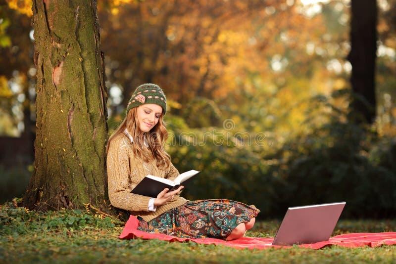 Jonge vrouw die een boek in een park leest stock afbeeldingen