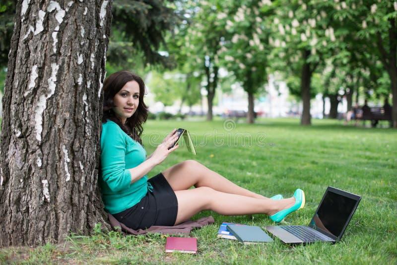Jonge vrouw die een boek in het stadspark lezen stock afbeeldingen