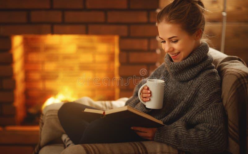 Jonge vrouw die een boek lezen door de open haard op de winter evenin royalty-vrije stock foto